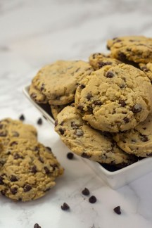 Chocolate chip cookies piled in a square white bowl with two cookies and a few chocolate chips to the side all on a white and grey marble surface (vertical)