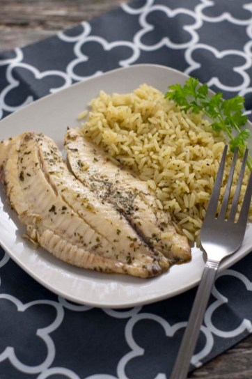Cilantro and lime juice covered fish fillets next to cilantro lime rice with a sprig of fresh cilantro on a square white plate with a stainless steel fork on a white and grey placemat on a wooden surface (vertical)