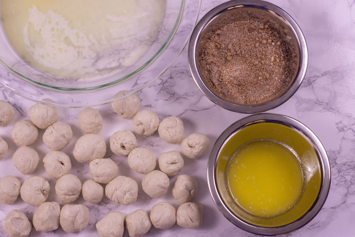 Rolled biscuit dough next to stainless steel bowls with cinnamon sugar in one and melted butter in the other with a glass pie pan with melted butter behind all on a white and grey marble surface