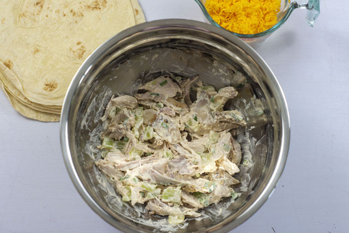Stainless steel bowl with sour cream mixture and rotisserie chicken mixed together next to a glass measuring cup of shredded cheddar cheese and tortilla shells all on a white surface