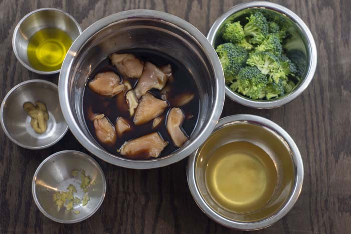 Stainless steel mixing bowl with chicken marinading in soy sauce surrounded by stainless steel bowls with oil, dijon mustard, minced garlic, chicken broth, and chopped broccoli all on a wooden surface