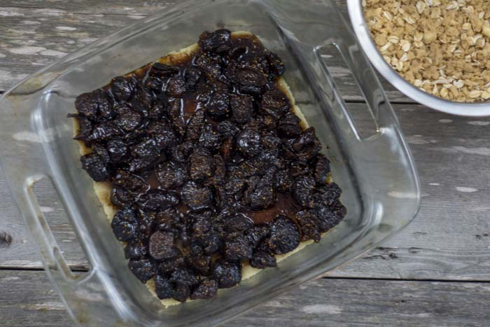 Glass baking dish with baked crust topped with cooked figs next to a stainless steel bowl with mixed streusel topping all on a wooden surface