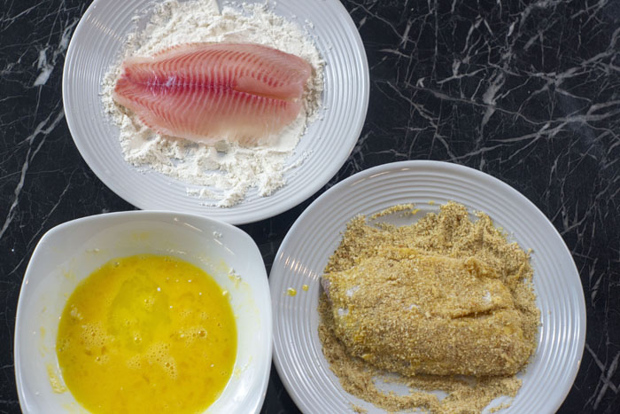 Round white plate with a fillet of tilapia on top of a bed of flour next to another white plate with a tilapia fillet covered in breadcrumbs with a round white bowl to the side with whisked eggs all on a black and white marble surface