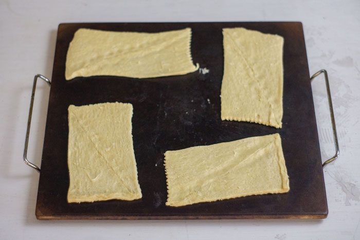Baking stone with rectangular crescent rolls on top on a white and grey surface