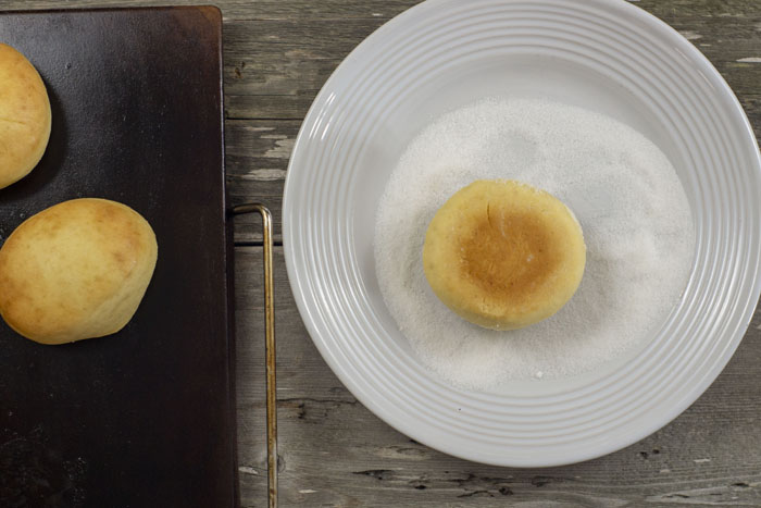 baked paczki on a baking stone next to a round white plate with a baked paczki in sugar all on a wooden surface