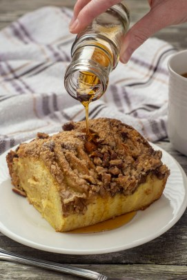 Piece of baked pancake casserole on a round white plate with maple syrup being poured on top next to a fork with a towel and cup of coffee behind all on a wooden surface (vertical)