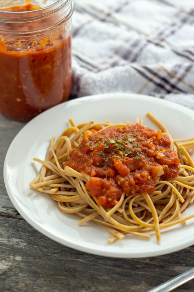 Spaghetti with homemade pasta sauce on a round white plate with a glass jar of pasta sauce behind next to a white and brown towel all on a wooden surface (vertical)