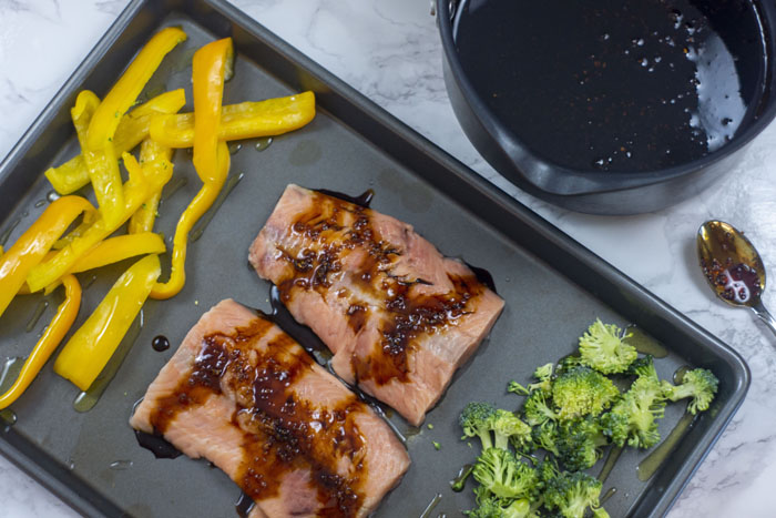 Metal sheet pan with two salmon fillets in the center surrounded by sliced yellow pepper and chopped broccoli all drizzled with some soy-molasses glaze next to a medium sauce pot of the remaining soy-molasses glaze and a spoon with glaze on it all on a white and grey marble surface