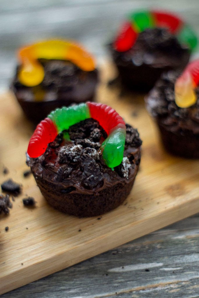 Dirt cupcakes covered with crushed oreos and topped with a gummy worm on a bamboo platter on a wooden surface (vertical)