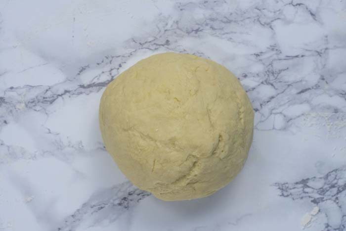 Rolled, kneaded king cake dough on a white and grey marble surface