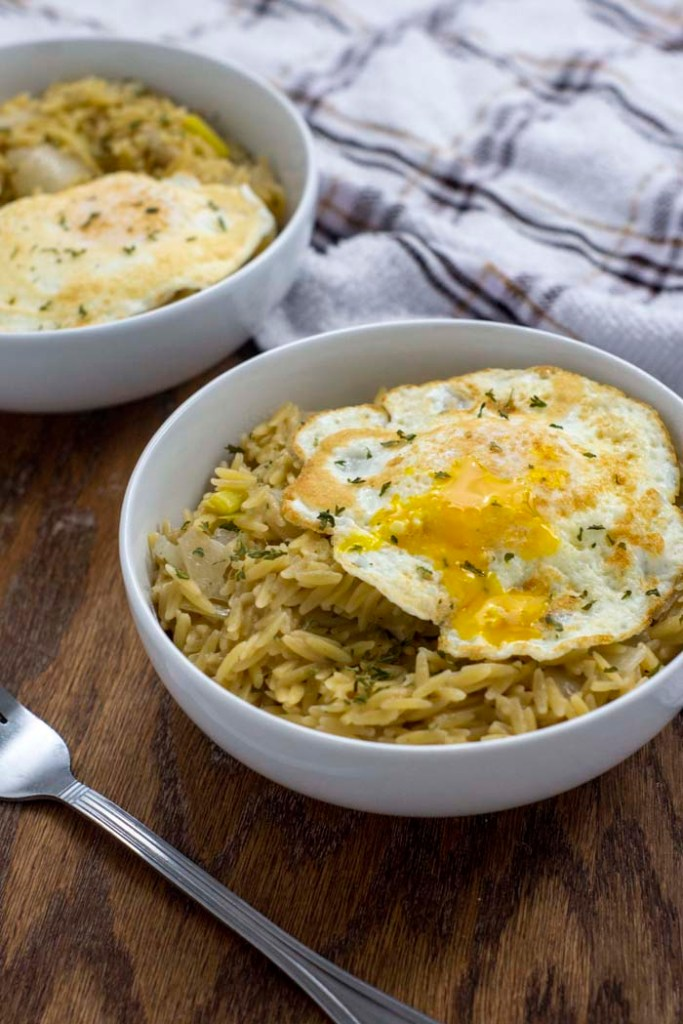 Leek orzo with fried egg garnished with parsley in two round white bowls with a stainless steel fork and a white and brown towel all on a wooden surface (vertical)