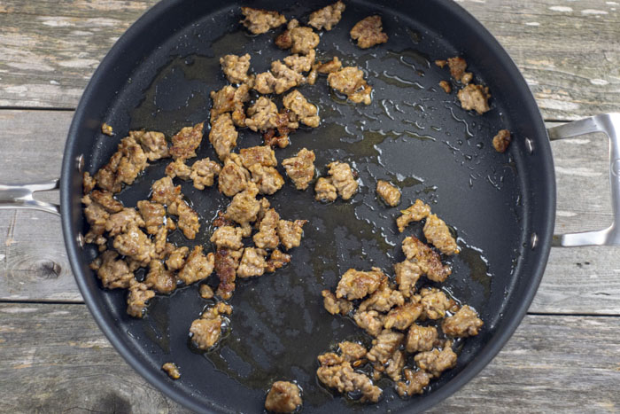 Crumbled cooked sausage in a large nonstick skillet on a wooden surface