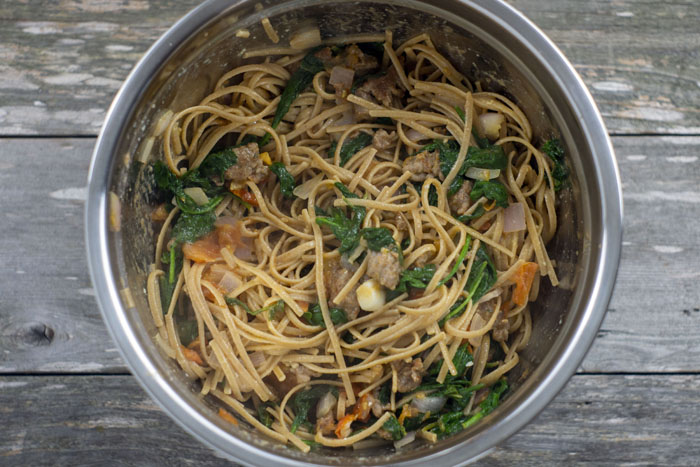Spaghetti noodles mixed with sausage, spinach, onions, and tomato in a stainless steel bowl on a wooden surface