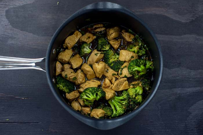 Chicken and broccoli in teriyaki sauce in a medium saucepan on a wooden surface