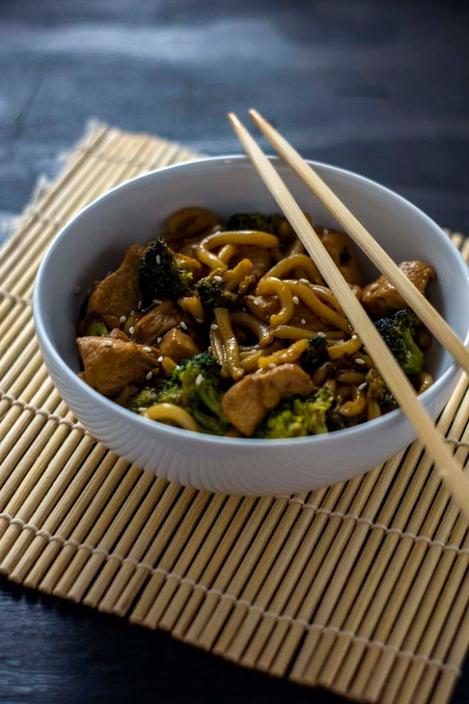 Teriyaki chicken with broccoli and udon noodles garnished with sesame seeds in a round white bowl with bamboo chopsticks on a bamboo mat on a wooden surface (vertical)