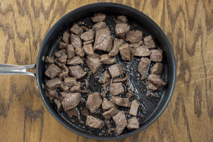 Cooked beef cubes in a nonstick skillet on a wooden surface