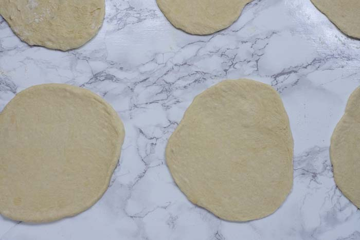 Flattened pita bread pocket dough on a white and grey marble surface
