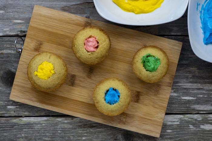 Cupcakes with the center cut out with colored frosting in the holes on a bamboo cutting board next to white bowls of yellow and blue frosting all on a wooden surface