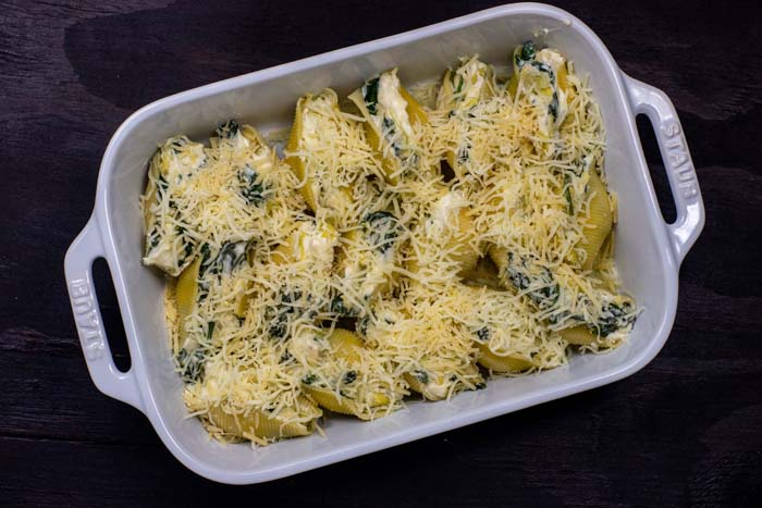 Pasta shells stuffed with spinach and artichoke mixture in a line topped with shredded cheese in a white casserole dish on a wooden surface