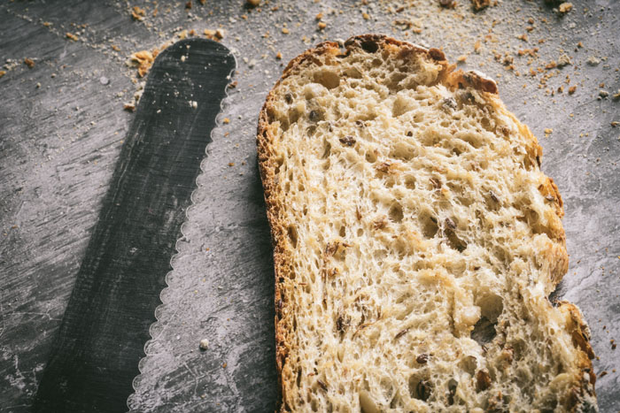 Bread knife next to a slice of bread
