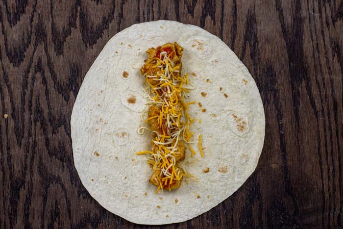 Cooked chicken and shredded cheese on a flour tortilla on a wooden surface