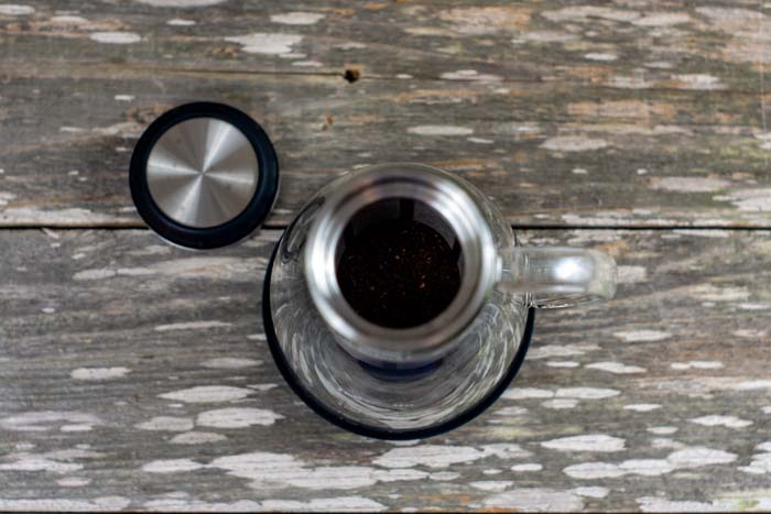 Overhead view of coffee grounds in the infuser of a cold brew coffee maker next to the lid on a wooden surface