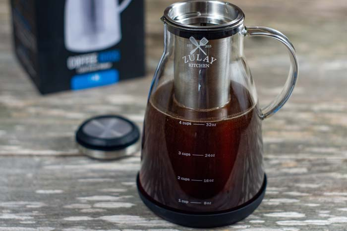 Cold brew coffee in a glass carafe with the lid and box behind on a wooden surface