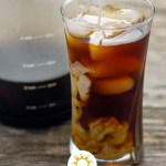 Cold brew coffee with cubes of ice in a glass cup with a carafe of cold brew coffee behind on a wooden surface (vertical with title overlay)