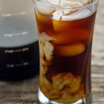 Cold brew coffee with cubes of ice in a glass cup with a carafe of cold brew coffee behind on a wooden surface (vertical with large title overlay)