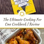 Front cover of The Ultimate Cooking For One Cookbook on a wooden surface with large title overlay in the center and a photo of bbq chicken drumsticks over veggies in a white casserole dish with a white and brown towel underneath on a wooden surface