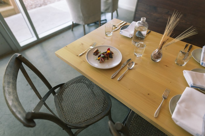 Wooden table set with plates and silverware with metal chairs around it