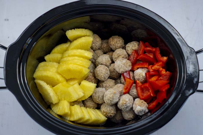 Pineapple chunks, frozen meatballs, and chopped red bell pepper in a slow cooker over a white surface
