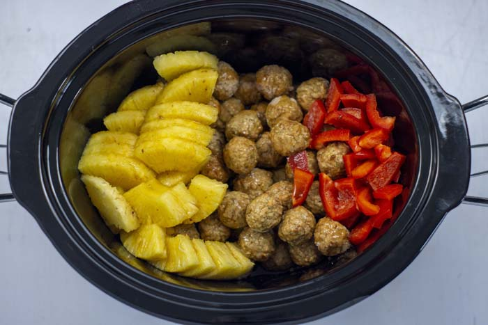 Pineapple chunks, meatballs, and chopped red bell peppers covered with Hawaiian sauce in a slow cooker on a white surface