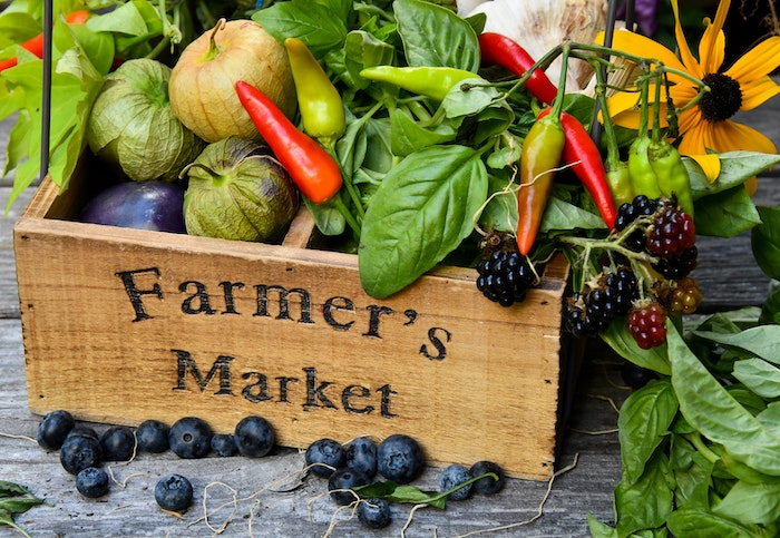 """Wooden box with the words """"farmers market"""" on the front filled with fresh fruits and vegetables"""