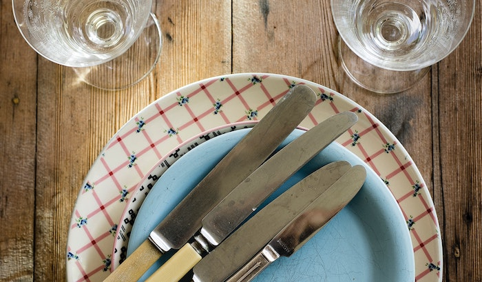 Patterned glass plates stacked with stainless steel butter knives on top with glass cups behind all on a wooden surface