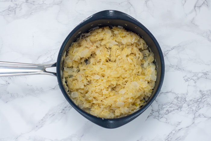 Sauerkraut and chopped onions in a saucepan on a white and grey marble surface