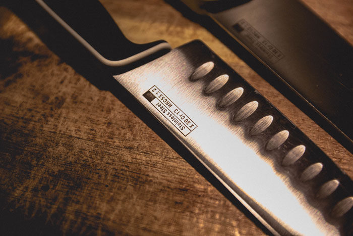 Santoku and chef kitchen knives on a wooden surface
