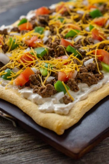 Baked taco pizza on a baking stone on a wooden surface (vertical)