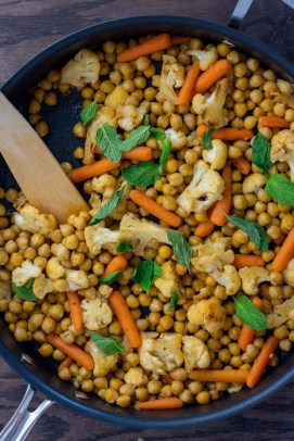 Chopped cauliflower, baby carrots, and chickpeas topped with mint leaves with a wooden spoon in a large nonstick skillet on a wooden surface (vertical)
