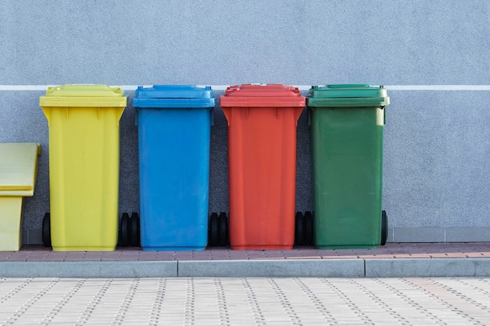 4 trash cans lined up on the side of a cobbled street