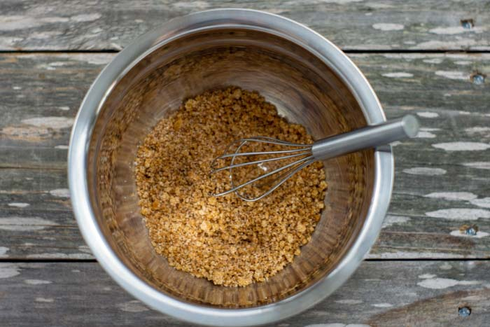 Brown sugar mixture in a stainless steel bowl with a wire whisk on a wooden surface