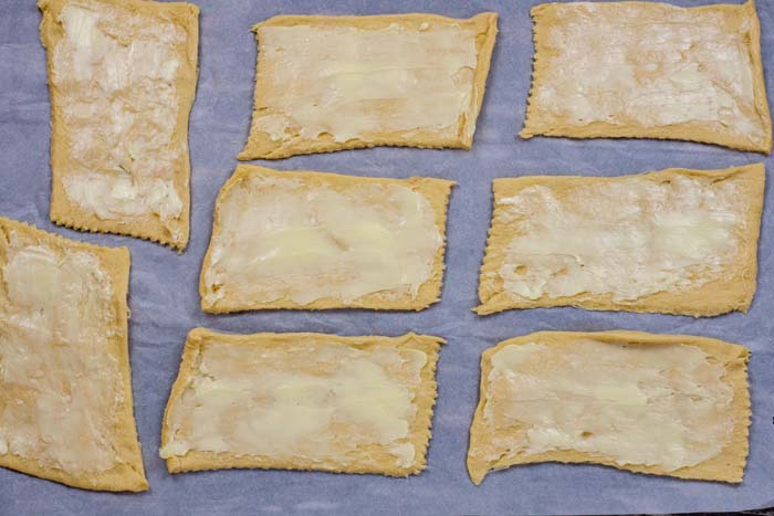 Flattened crescent rolls covered with butter on parchment paper