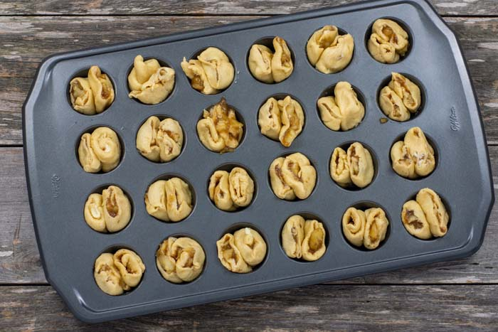 Sticky buns in a mini muffin pan on a wooden surface