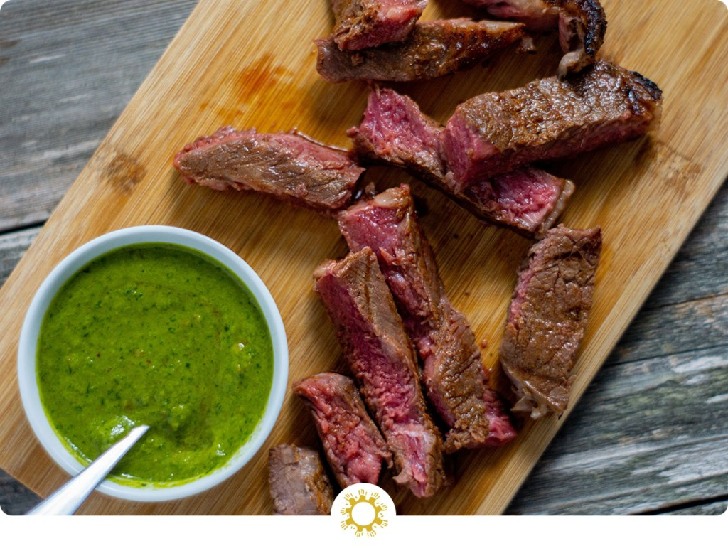 Slices of brown sugar steak next to a white bowl of green chimichurri sauce on a bamboo cutting board on a wooden surface (with logo overlay)