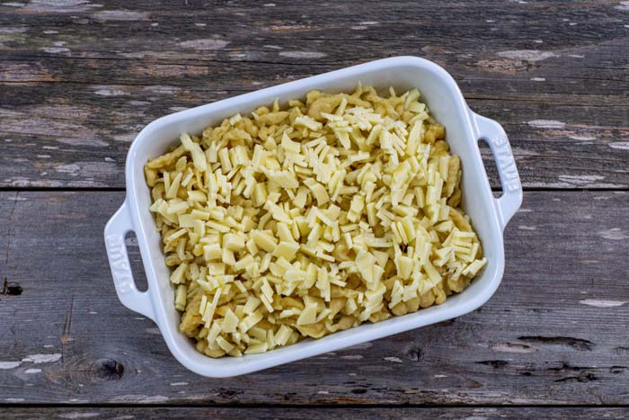 Spaetzle noodles topped with cheese in a white casserole dish on a wooden surface
