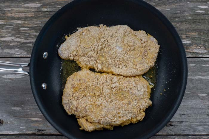 Two breaded chicken breasts in a skillet over a wooden surface