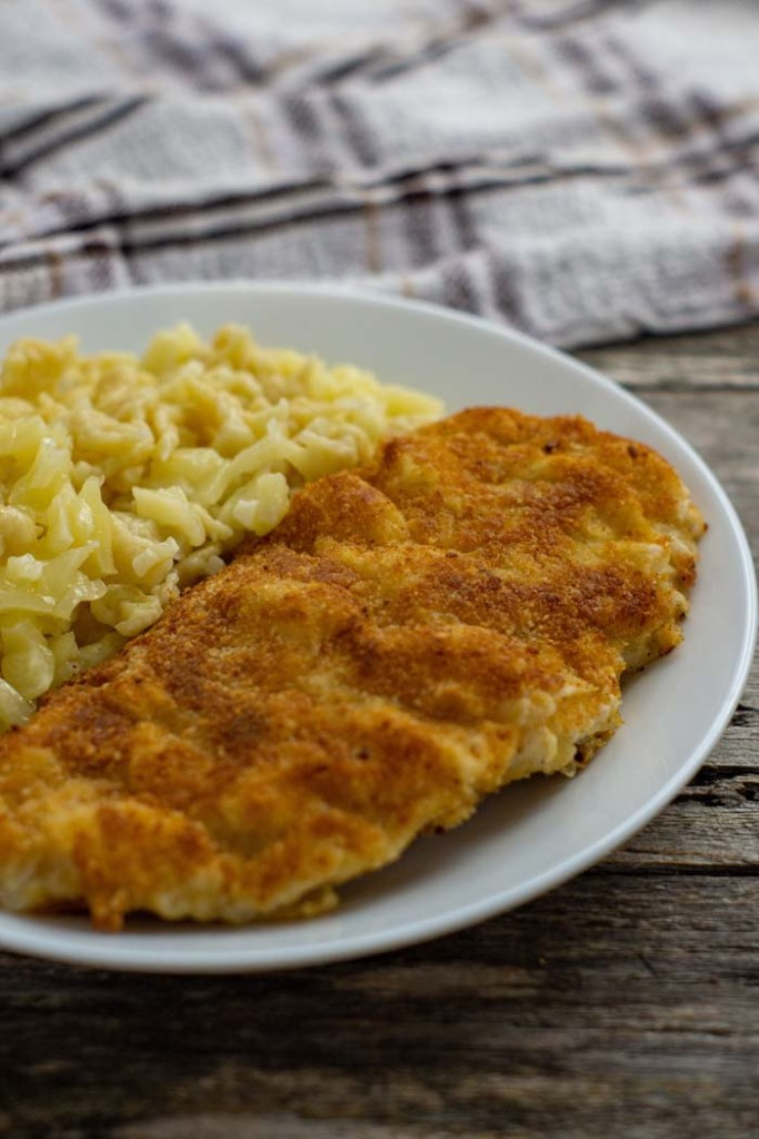 Chicken schnitzel next to cheesy spaetzle on a round white plate with a white and brown towel behind all on a wooden surface