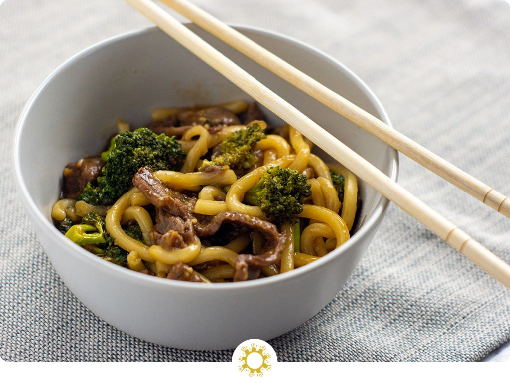 Beef and broccoli with udon noodles in a round white bowl with wooden chopsticks on a grey placemat all on a white surface (with logo overlay)