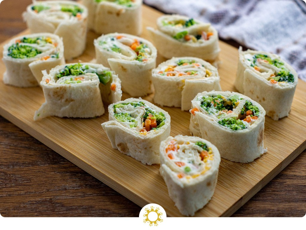Veggie tortilla pinwheels on a bamboo tray with a white and brown towel behind all on a wooden surface (with logo overlay)