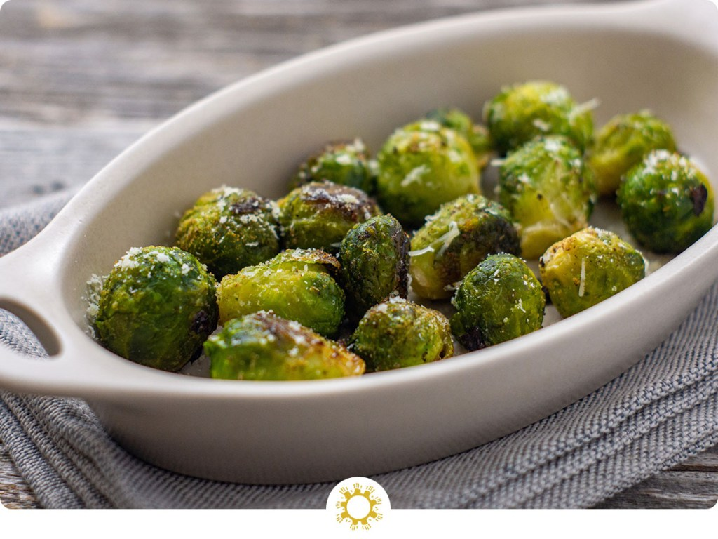 Garlic-Parmesan Brussels Sprouts in a white oval dish on top of a grey napkin on a wooden surface (with logo overlay)